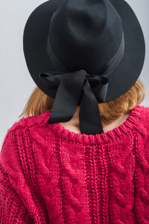 Young woman dressed black hat with bow, knitted large viscous pink sweater , Back view. White background. Imagens