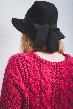 Young woman dressed black hat with bow, knitted large viscous pink sweater. White background.