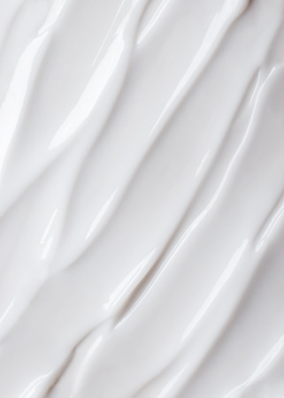 Close-up brushstroke of face cream on white background. Copy space. Foto de archivo