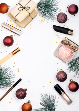 Set of beauty products: lipsticks, liquid eyeshadow, bronze face powder, perfume, packaged Christmas gifts sprinkled with golden small stars decor on white background.