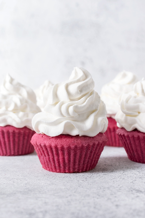 Pink cupcakes with whipped cream on top on textured light gray-white surface.