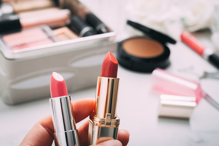 Woman's hand holds two lipsticks. Beauty products blurred background. Copy spase. Standard-Bild