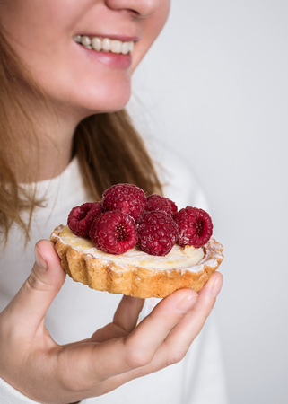 Woman holds cheese cake with fresh raspberries on top.