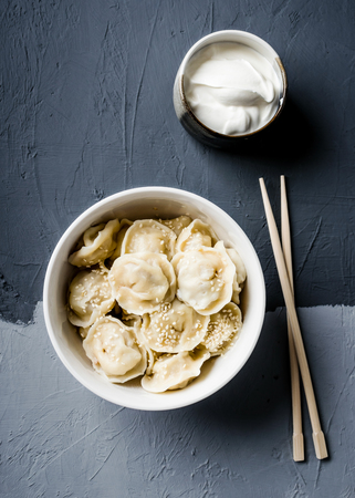 Cooked dumplings are served in a white bowl with sesame seeds on top, cream sauce and chopsticks on a gray textured surface.