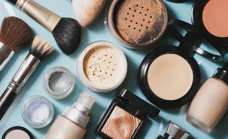 Set of decorative cosmetics. Face powder, concealer, eye shadow, blush, foundation. Blue background.