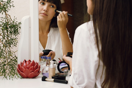 Girl doing makeup. White dressing table. Home interior.