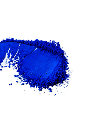 Deep blue brush stroke of eye shadow on white surface.