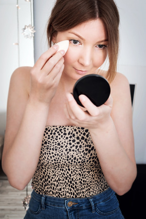 Close-up portrait of girl doing make-up, looking on herself at mirror and applying foundation on cheek using makeup sponge.