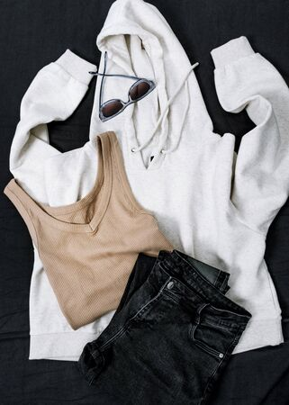 white hoody, beige tank, black jeans sunglasses on black surface . Top view.
