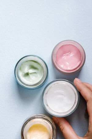 A person picking up open face cream jar. Top view.
