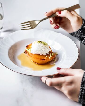 Woman with dessert on a plate, baked quince with ice cream and pistachio.