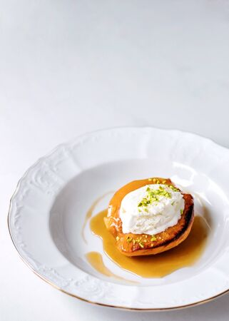 Baked juicy caramelized quince with ice cream and pistachio served on white plate. Banco de Imagens