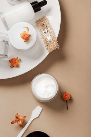 Face care cosmetics and fresh cloudberry on beige background.