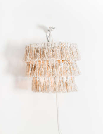 electric lamp with handmade shade hanging on the wall