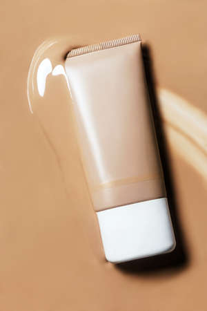 A tube of foundation on surface covered with liquid foundation.