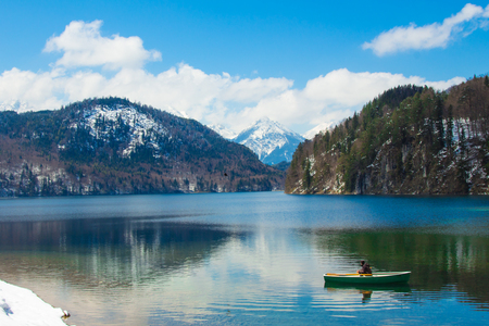 alone man on the boat on lake in Germany, Alpsee