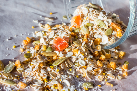 Plate of homemade muesli with pumpkin seeds, flower dust, candied fruit, freeze dried apricot. Scattered Фото со стока