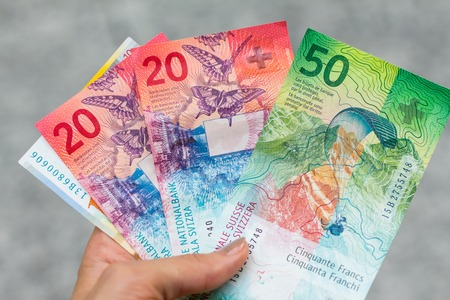 Set of swiss franc banknotes isolated on grey background in hand Stock Photo