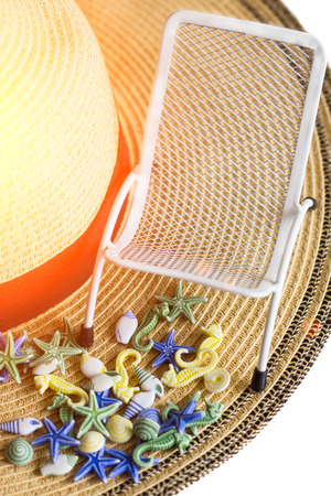 Seashells, sunbeds on background of summer straw hat, isolated Фото со стока
