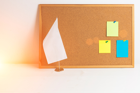 Colorful different stickers pined on the corkboard and white flag staying on wooden white table, horizontal. Flag with place for text