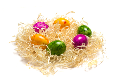 Colored eggs on packing straw. Isolated. Easter 2018 Stock Photo