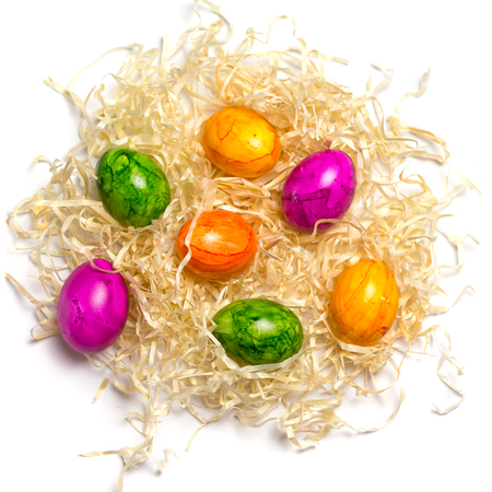 Colored eggs on packing straw. Isolated. Easter 2018. Top view. Stock Photo