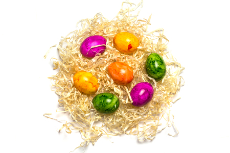 Colored eggs on packing straw. Isolated. Easter 2018 Top view.