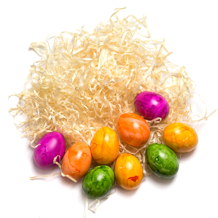 Colored eggs on the side of packing straw. Isolated. Easter 2018. top view. Stock Photo