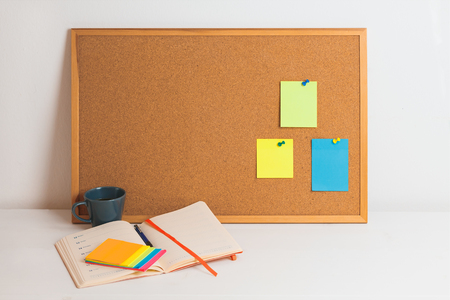 Colorful different stickers pined on the corkboard with notepad and coffe on white wooden table, horizontal Reklamní fotografie