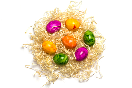 Colored eggs on packing straw. Isolated. Easter 2018 Top view