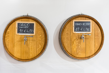 Wooden barrels for wine with a tap in wine shop. Close-up. Wine for bottling. Price for one liter wine. Top view.