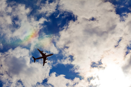 Airplane in the blue sky with white clouds, background. Rainbow against the sky.