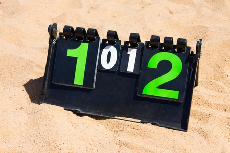 Close up of sport volleyball scoreboard on the summer sand. Score - tie, 1-1.