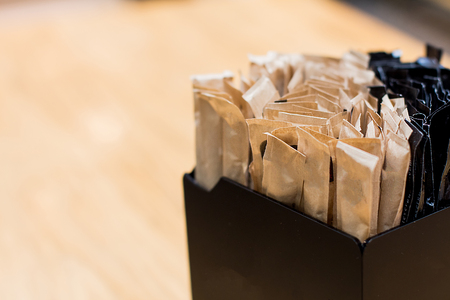 Brown sugar sachets in black box on a counter at a cafe