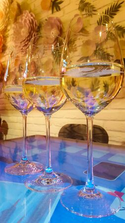 Three glasses of white wine with some residual effervescent bubbles out-gassing on table in bar. Vertical