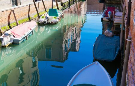 Closed up water of canal in early morning light. Old narrow canal with parked boats, Venice, Italy