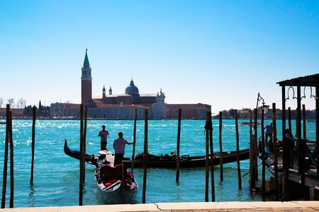 A panoramic view to the Venice lagoon, San Giorgio Maggiore island, to gondolas with tourists and gondolier moving to the San Marco pier in a spring sunny day