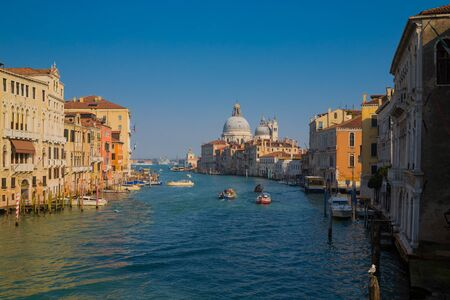 Panoramic view of famous Canal Grande and Basilica di Santa Maria della Salute at sunset in Venice, Italy.