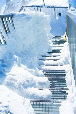 Top view of steel winding stairs on a winter day. Steps littered with snow. Vertical. Standard-Bild