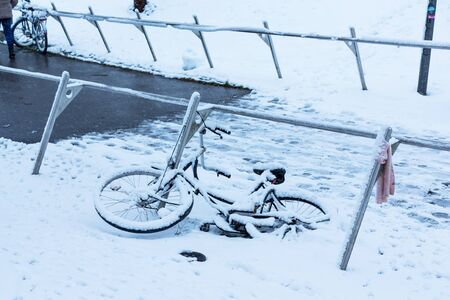 Black bicycle lies under the snow outside after a snowfall in town.