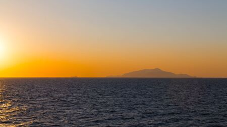 Cargo ships in sunset with contours of the islands. 写真素材