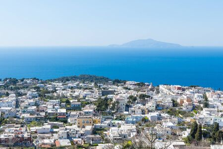 Town of Capri, Italy with white houses, blue sky and blue water. View of Mount Vesuvius. 스톡 콘텐츠 - 131952490