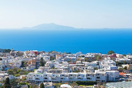 Town of Capri, Italy with white houses, blue sky and blue water. View of Mount Vesuvius.