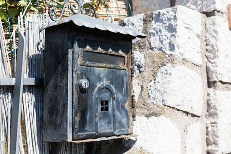 Old black Poste Italiane mailbox on grey grungy wall in Capri, Italy.