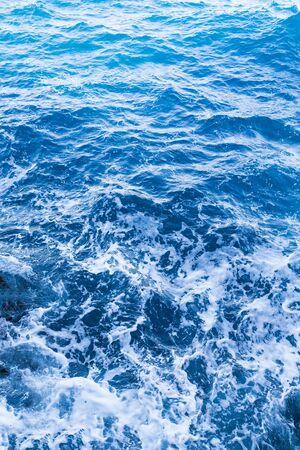 Background blue waves of the sea with sea foam. Zdjęcie Seryjne
