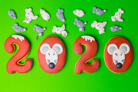 New year 2020 numbers cookies or biscuits with icing and the image of a mouse or rat on the number zero, christmas tree. Marshmallows in the shape white and gray mice or rats. Green background. 写真素材