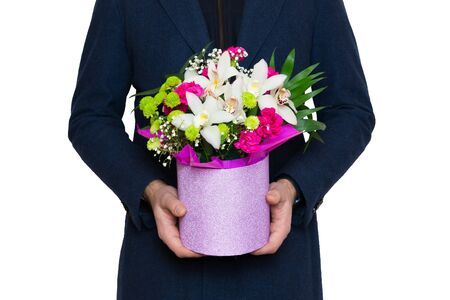 Man in blue coat holding a beautiful bouquet in a pink luxury round hat box with white Orchids, red Carnations, green Chrysanthemums, isolated on white background. Gift for woman. Banque d'images - 138464835