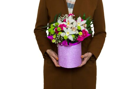 Woman in brown coat holding a beautiful bouquet in a pink luxury round hat box with white Orchids, red Carnations, green Chrysanthemums, isolated on white background. Gift for man. Banque d'images - 138465317
