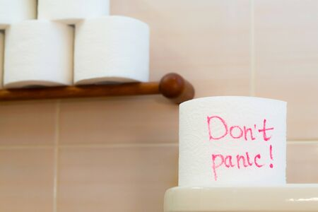 Text- Dont panic on the toilet paper. A roll of toilet paper on the background of several rolls.