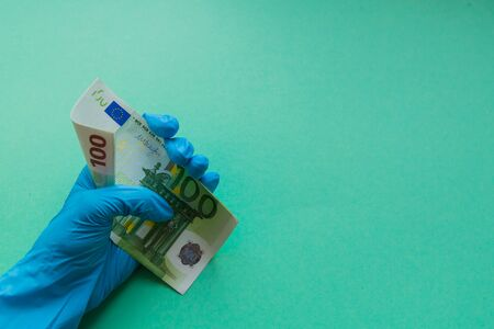 Hand protective glove holds euro banknote. Financial crisis in Europe because of the coronavirus concept. Banco de Imagens